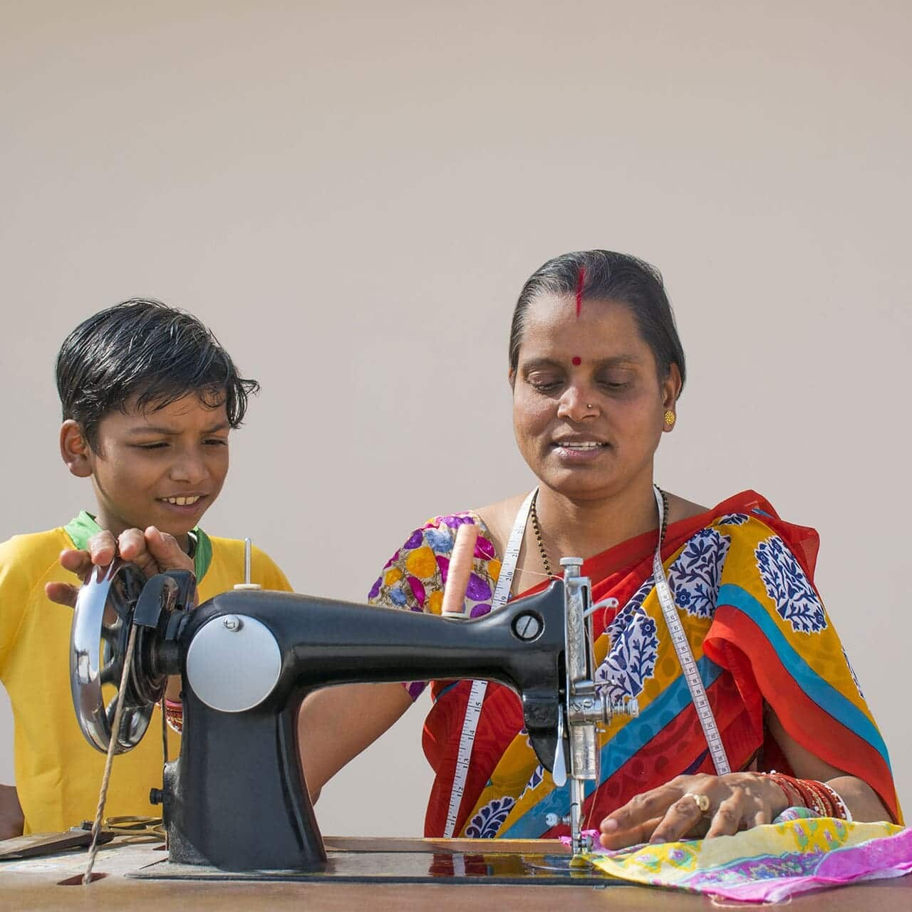 indian woman and boy sewing